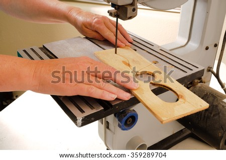 Closeup of a woman's hands working with a band saw to cut an intricate shape in a piece of plywood - stock photo
