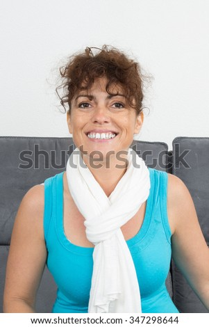 Closeup of a woman smiling at the camera with blue top and white scarf - stock photo