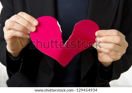 Closeup of a woman tearing apart a heart - stock photo