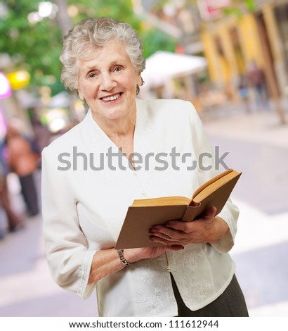 Closeup Of A Woman While Holding Book, Outdoor - stock photo