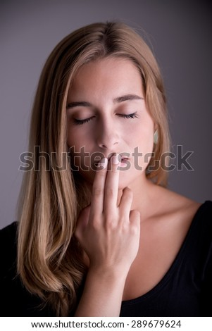 Closeup of a woman with her finger over her mouth - stock photo