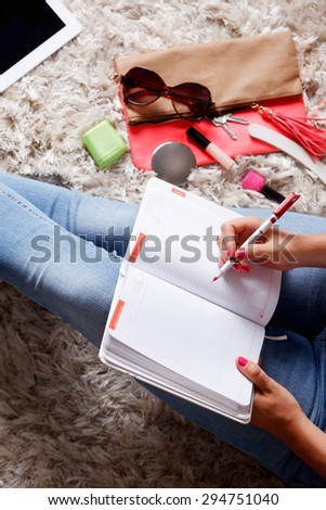 Closeup of a woman writing into her desk diary - stock photo