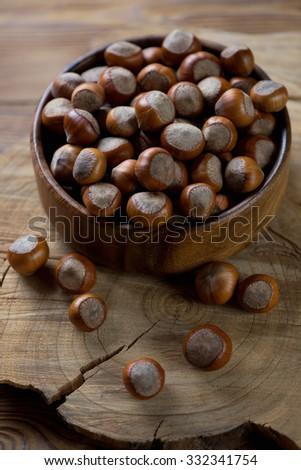 Closeup of a wooden bowl with hazelnuts, selective focus