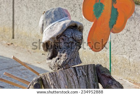 Closeup of a Wooden Puppet made by Pieces of a Tree Trunk holding a Big Painted Orange Flower - stock photo