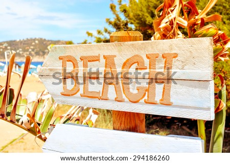 closeup of a wooden signpost with the text beach written in it, in Ibiza Island, Spain, with a filter effect - stock photo