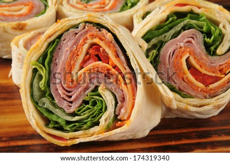 Closeup of a wrap sandwich with salami, pepperoni, and cheeses - stock photo