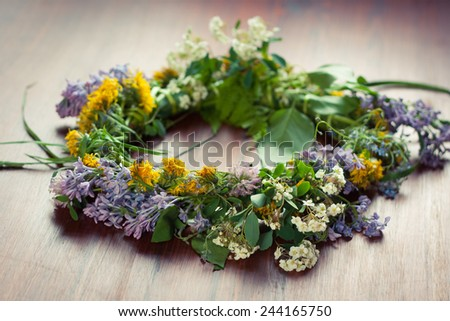 Closeup of a wreath of wild spring flowers on a wooden table - stock photo