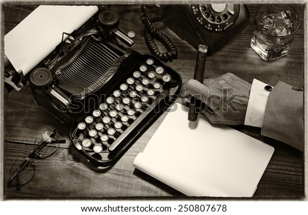 Closeup of a writer at his desk with a typewriter, rotary telephone, glass of whiskey and a cigar. Black and white toned image for a vintage feel. Only the mans hand holding a cigar is shown. - stock photo
