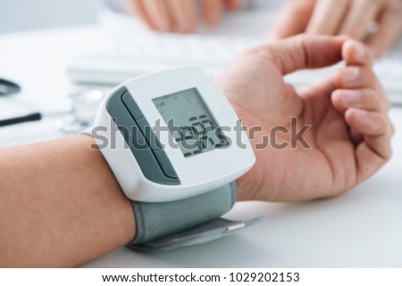 closeup of a young a caucasian patient man at the doctors office whose blood pressure is being measured with a sphygmomanometer, which shows a high blood pressure
