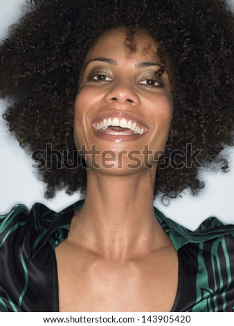Closeup of a young afro woman with curly hair laughing against white background - stock photo
