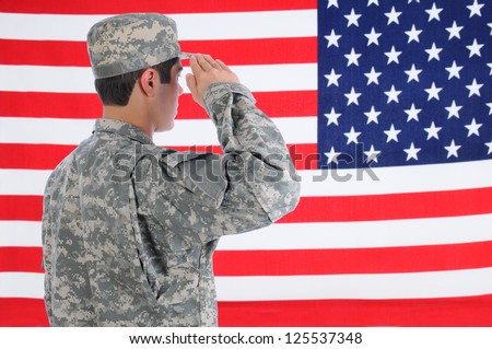 Closeup of a young American Soldier in Fatigues saluting the Flag. Flag fills the frame and is out of focus. Man is seen from behind. - stock photo