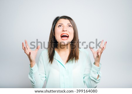 closeup of a young angry woman shouting  - stock photo