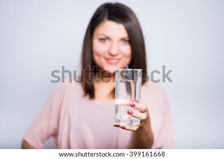 closeup of a young beautiful woman gives drink a glass of water