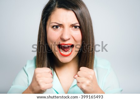 closeup of a young beautiful woman rejoices victory with fists