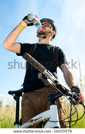 closeup of a young biker drinking water