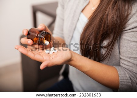 Closeup of a young brunette getting some aspirins from a bottle at home