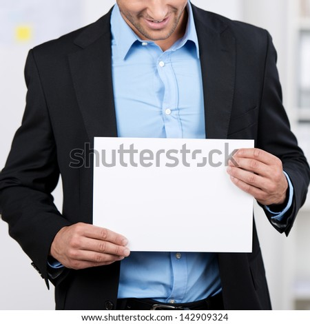 Closeup of a young businessman showing a blank white sheet.