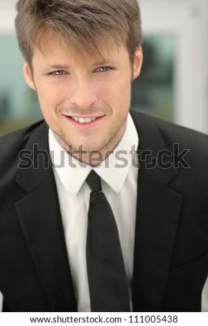 Closeup of a young businessman smiling - stock photo