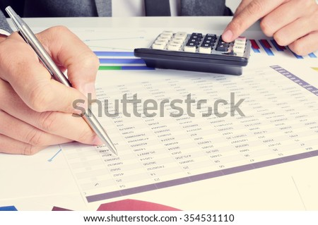 closeup of a young caucasian businessman checking accounts with a calculator in his office - stock photo