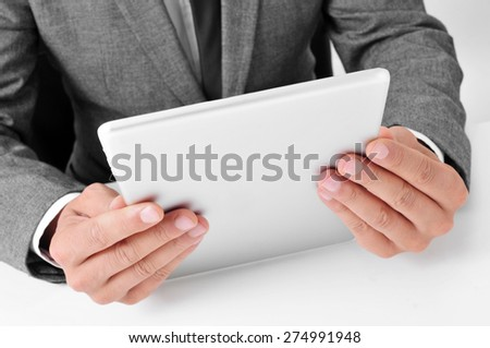 closeup of a young caucasian businessman in gray suit sitting at his office desk uses a tablet computer - stock photo