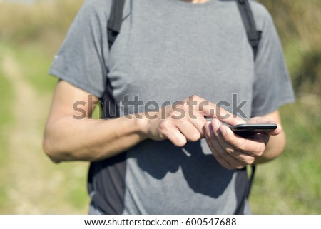closeup of a young caucasian man carrying a backpack using a smartphone outdoors