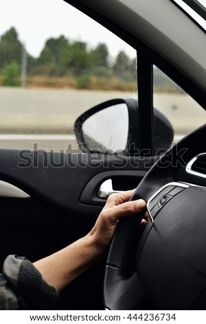 closeup of a young caucasian man driving a car in a road with several lanes, in a rainy day