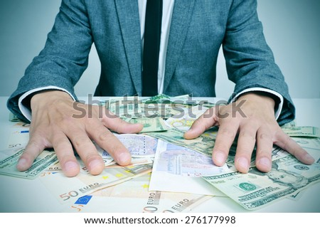 closeup of a young caucasian man in suit sitting at his office desk full of euro and dollar bills trying to hold them, depicting wealth or greediness - stock photo