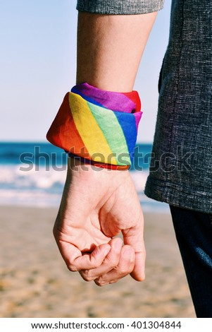 closeup of a young caucasian man seen from behind with a kerchief patterned as the rainbow flag tied in his wrist, with the ocean in the background - stock photo