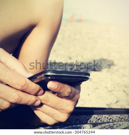 closeup of a young caucasian man using a smartphone on the beach, with a filter effect - stock photo