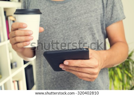 closeup of a young caucasian man wearing a gray t-shirt and with a cup of coffee in his hand uses a tablet computer indoors - stock photo