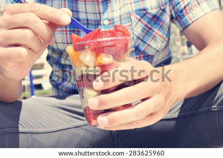 closeup of a young caucasian man wearing a plaid shirt eating a fruit salad in a clear plastic cup outdoors - stock photo