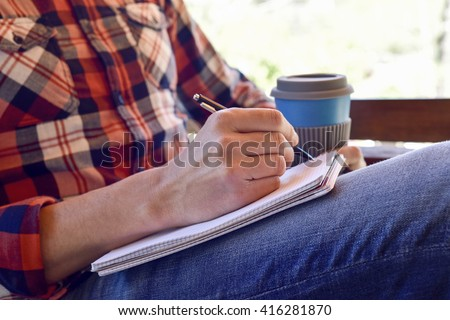 closeup of a young caucasian man wearing jeans and a plaid shirt writing with a pen in a notebook - stock photo
