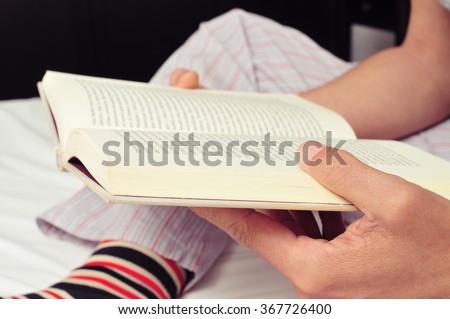 closeup of a young caucasian man wearing pajamas and colorful striped socks reading a book in bed - stock photo