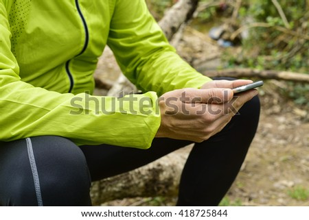 closeup of a young caucasian sportsman wearing sport clothes outdoors seated on a tree trunk using his smartphone - stock photo