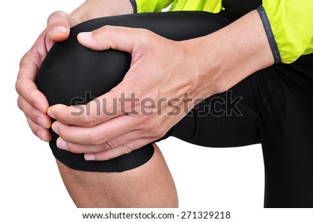 closeup of a young caucasian sportsman wearing sport clothes with his hands in his knee because of his knee pain - stock photo