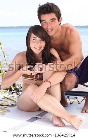 Closeup of a young couple sailing a catamaran - stock photo