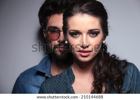 closeup of a young couple smiling and looking at the camera in studio - stock photo