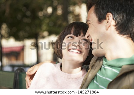 Closeup of a young couple smiling at each other on park bench - stock photo