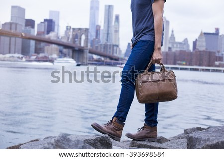 Closeup of a young entrepreneur going for a walk, wearing boots and a briefcase in New York - stock photo