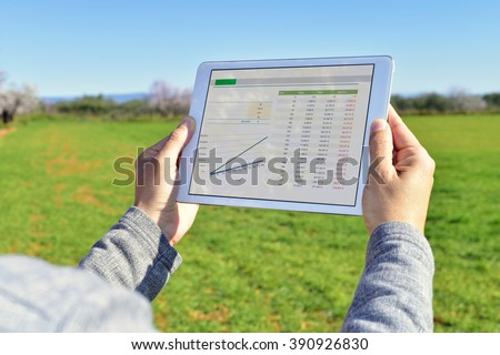 closeup of a young farmer observing some charts in a tablet computer in a fallow field - stock photo