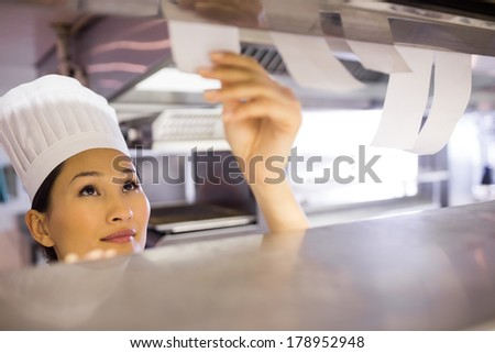 Closeup of a young female chef going through cooking checklist at kitchen counter - stock photo