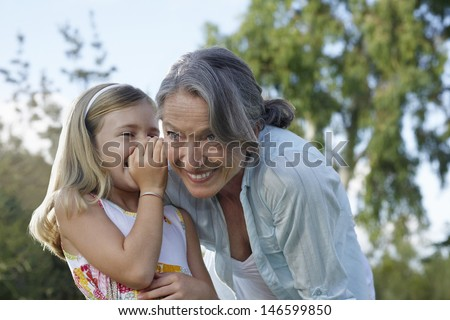 Closeup of a young girl whispering in grandmother's ear outdoors - stock photo