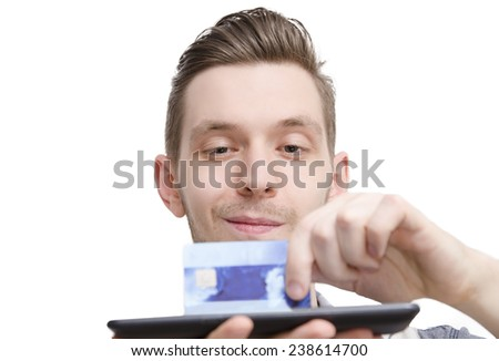 Closeup of a young guy holding credit card on a tablet. Online shopping concept, selective focus on a guy. Money transaction concept - stock photo