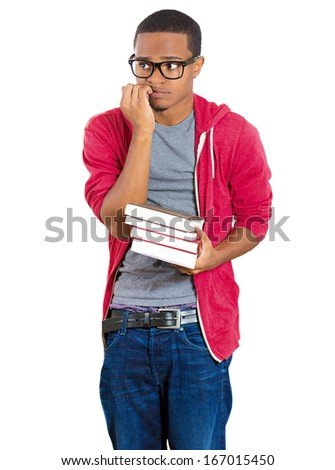 Closeup of a young handsome man wearing big glasses, holding books, biting fingernails anxiously in anticipation of finals, isolated on white background. Negative emotion facial expressions, feelings - stock photo