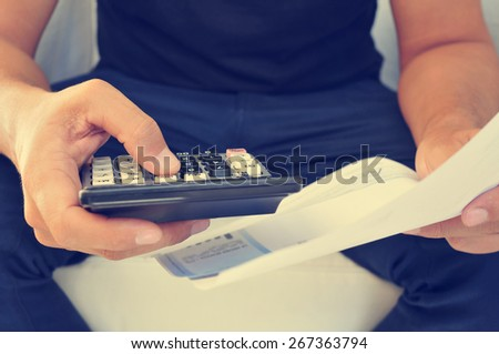 closeup of a young man checking a bill, a budget or a payroll with a calculator, filtered effect - stock photo
