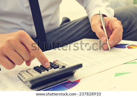 closeup of a young man checking accounts with a calculator - stock photo