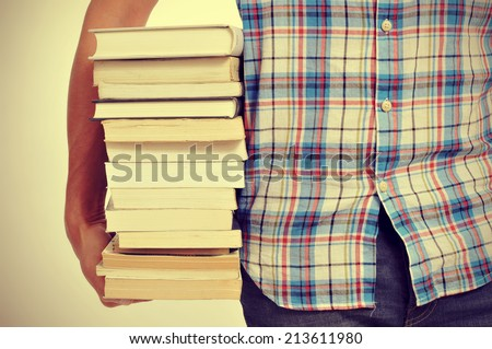 closeup of a young man holding a pile of books, with a filter effect - stock photo