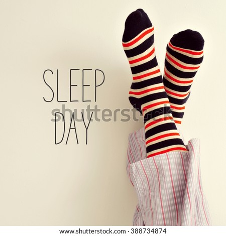 closeup of a young man in pajamas wearing colorful striped socks with his feet against the wall and the text sleep day - stock photo