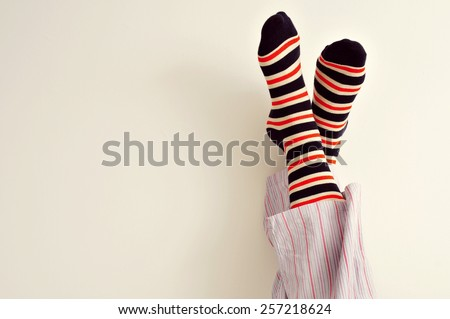 closeup of a young man in pajamas with his feet against the wall - stock photo