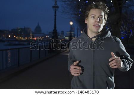 Closeup of a young man jogging at night - stock photo
